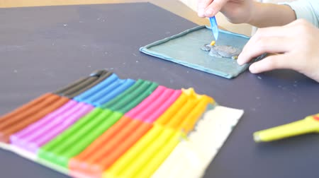plastelíny : the girl sitting at the table, draws different figures from color model plasticine. Development of art modeling in children. 4k, close-up, slow-motion