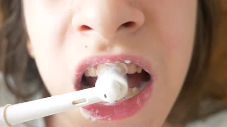 лечение зубов : The child cleans his teeth in front of a mirror in 4k. girl teenager brushes teeth with electric toothbrush, close-up, slow-motion shooting