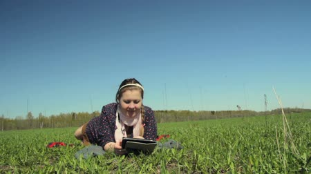 in : Girl lying on the grass with the tablet. Camera movement with the slider Stock Footage