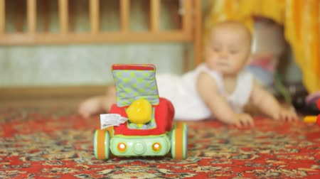 toy : Baby crawling on the floor and look at the moving car. Filmed with slider