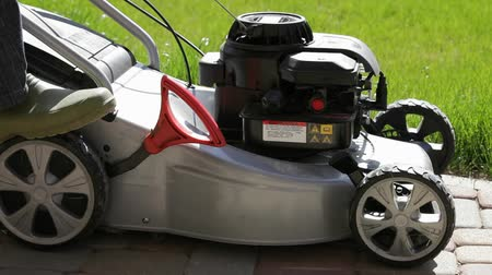 yards : Mans hand pushing the red button to pump up petrol. Man pulls recoil starter. Lawnmower start. Stock Footage