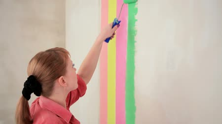 проект : Girl roller of a krasitn to a wall of a strip of different color.