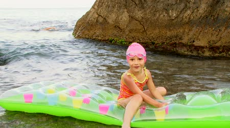 inflável : Cute little girl in a rubber cap and goggles swims in the sea on inflatable mattresses.