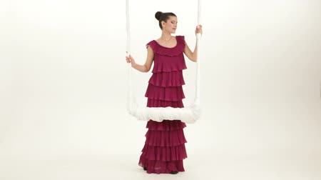 brown dress : LONG SHOT. The girl in the purple evening dress singing about swing on a white background