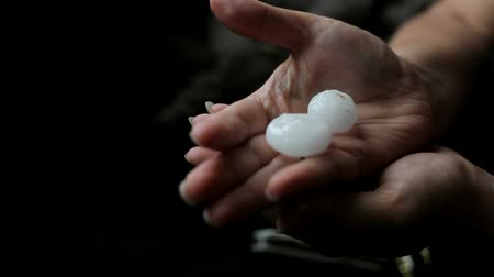 womans hand : Hail larger than two centimeters is on the hand of a woman. Movement of focus and dark background. Stock Footage
