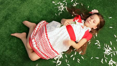 piada : Little girl dressed in a red polka-dot dress resting on artificial turf and tears off the the petals of daisies.