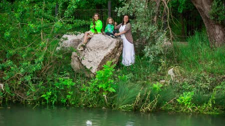 adore : This is a picturesque view of a family of three - mother, daughter and small son - standing and sitting on the rock near pond and throwing stones into it. Lush greenery is growing around.