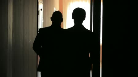 siluety : Silhouette of two young man from the back walking along the corridor.