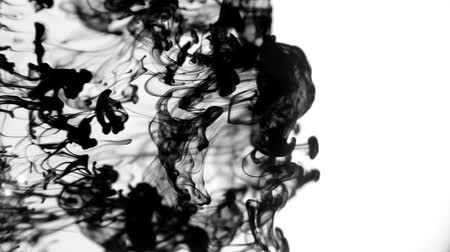black dirt : Drops of black ink flowing through water creating abstract wispy pattern.