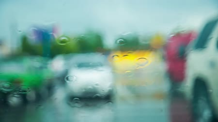 outside view : This is footage at stormy day - drops of rain gently falling on car glass and flowing down during rainstorm in the city. Parking with lots of standing cars some of them are moving in opposite directions on blurred background. Stock Footage