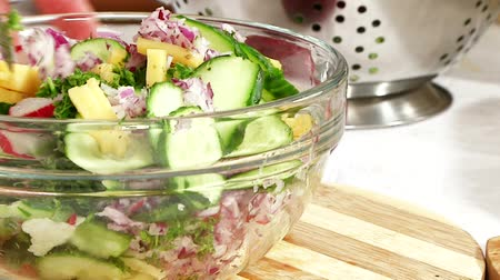 salad : Cook mixes the ingredients for the salad. Cucumbers  radishes  cheese  red onion  dill  parsley.