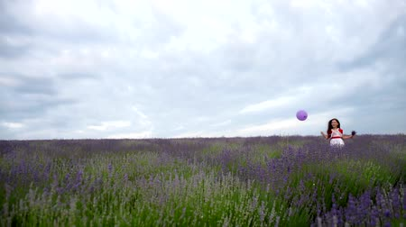 jump away : Girl laughs and fun jumps. Long hair fluttering in the wind.  Child with purple ball runs through lavender field.