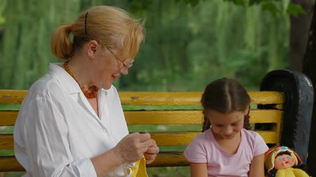 boneca : Woman working with a crochet in a park near her granddaughter