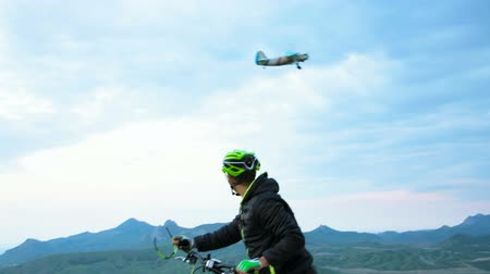 pursuit plane : Three frames: in first frame there is a side view of a mountain biker admiring the wide shot of a picturesque valley with many hills covered with greenery and the mountain range. In the second he meets and salutes a small plane flying not very high. In th