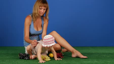 toy : Woman sitting on green grass with her child.