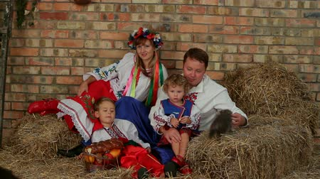 cegła : A large family dressed in traditional costume resting at the farm.