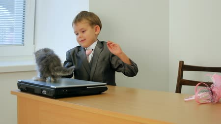kotě : A little boy in a business suit sitting at a table and played with a kitten. Two frames.