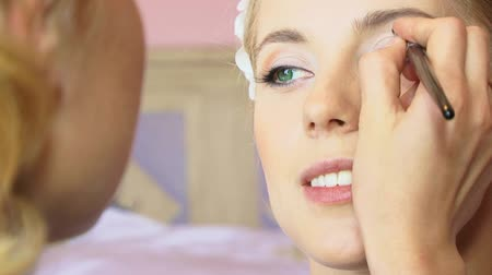eyeshadow : Beautician working with bride. Wedding Make-Up Stock Footage