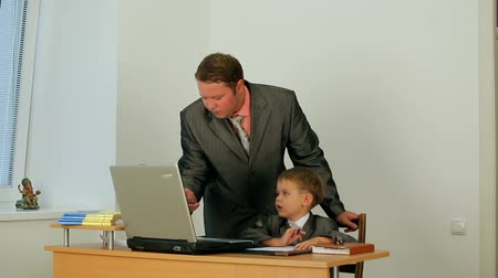 heir : A man in business suit working with his son.