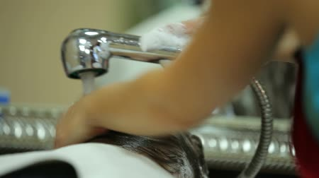 şampuan : Girl is washing clients hair. Close up.