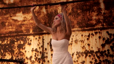 devastated : The bride in a wedding dress, stands and looks at old and rusty wall. Motion zoom.