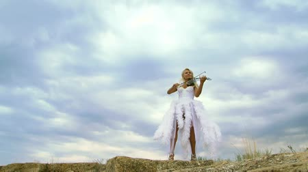 tündér : Beautiful girl in a fairy dress playing the violin at the background of a beautiful sky. Stock mozgókép