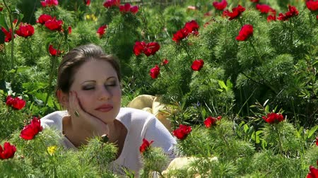 olhos verdes : A beautiful young girl lying among the red flowers and laughs.
