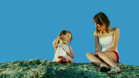 gentleness : Two girls sit on a rock and talk.
