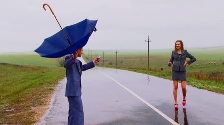 cena não urbana : There is a strong rain. Two joyful people try to catch a signal by a mobile phone. The guy uses an umbrella as the aerial. Against the background of the wet roads and green fields. Vídeos