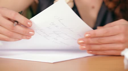 letras : Beautiful girl sitting at a table writing a letter. Close up.