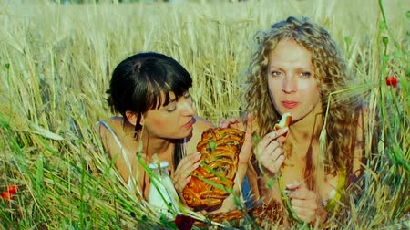 leite : Two charming young women are at the wheat field. Eat bread, drink milk, talk.