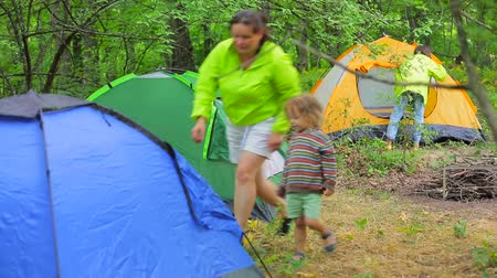 clearing away : Family hike. The forest is a campground. My mother and the little boy go into the tent. Stock Footage