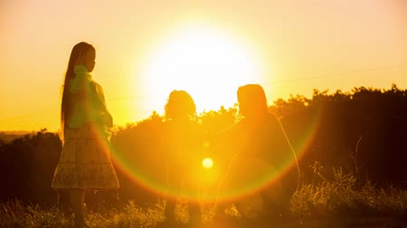 radość : Silhouette of a happy family of three - mother, daughter and small son dancing at nature. In the beginning mother dancing only with son, in a while  a daughter joins them. The shot was captured at the nature at beautiful sunset with sun shining directly t