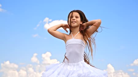 radość : In the frame there is a happy pretty little girl with long brown hair in white sundress jumping with joy raising hands enjoying summertime on cloudy sky background.