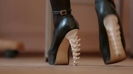 vysoký : Female feet in shoes with heels in the shape of the spine. Slow motion video.