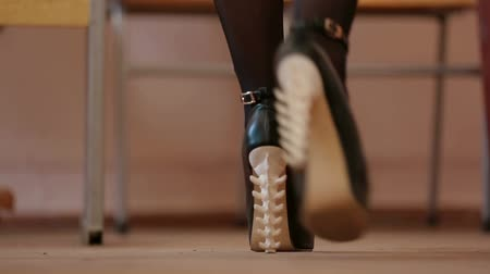 pięta : Female feet in shoes with heels in the shape of the spine. Slow motion video.