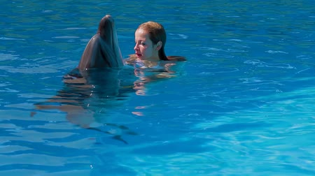 yunus : This is a shot of a young woman and dolphin training in blue crystal water of a pool.