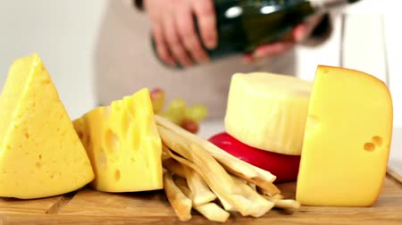 rokfor : A woman prepares a snack of cheese with white wine. Stok Video