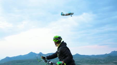pursuit plane : Mountain Biker Meeting Small Airplane At Hilly Terrain