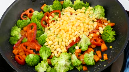 pour corn kernels into a frying pan with fried vegetables Stok Video