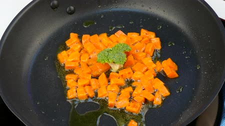 brócolis : fry pieces of carrots in oil in a frying pan with broccoli