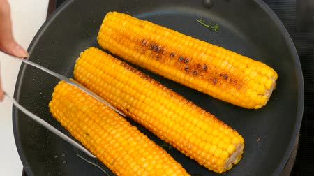 turn the cooked corn cobs in a frying pan Stok Video
