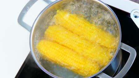 Open the saucepan with corn in boiling water