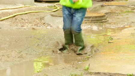 boy with an umbrella jumping in a puddle