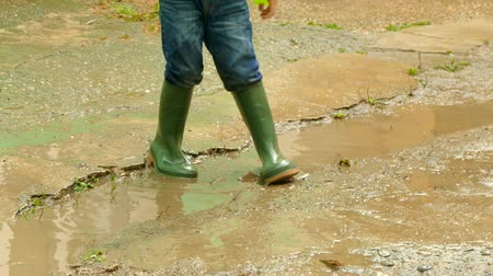 child having fun in rubber boots in a puddle