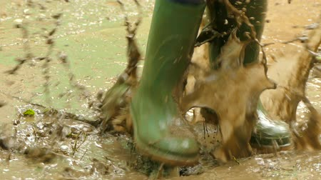 in rubber boots jumping over dirty puddles Stok Video