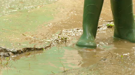 goma : in rubber boots run through the puddles Stock Footage