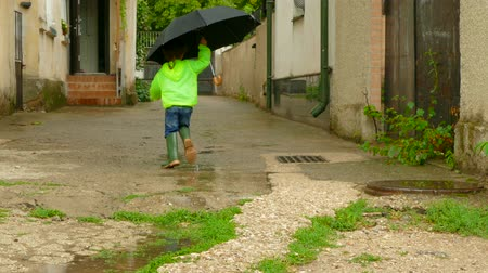grime : boy with an umbrella running around the yard in rubber boots Stock Footage