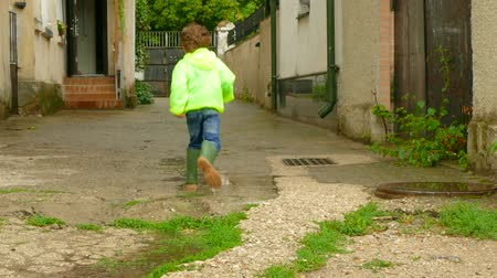 the boy in the raincoat runs around the yard in rubber boots Stok Video