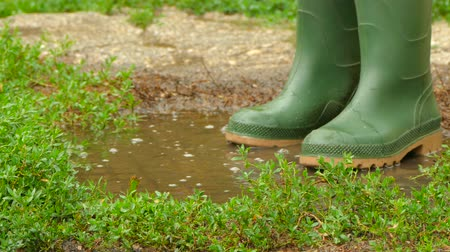 grime : feet in rubber boots fun to jump across the puddle